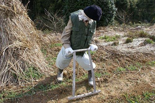 ホオリマンガ(耕した畑の土の塊を砕く道具)をするおじさん。