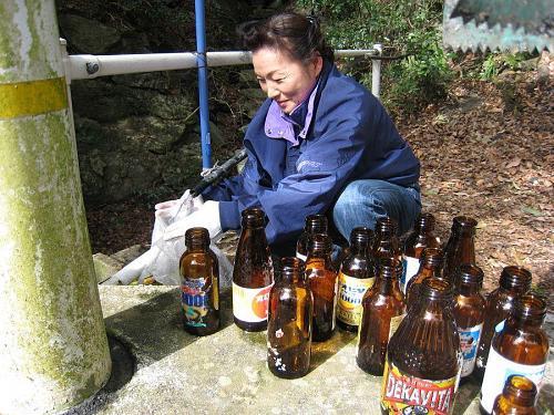 ヒロコおばさんは空きビンの洗浄中。ビンの中を洗って乾かして、空きビン専用袋に入れて、リサイクル。割れたビンやアルミキャップは、その他の不燃物で埋め立て処分。