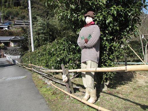 神木橋付近、椿の脇で佇むカカシさん。赤いマフラーと緑の手袋が格好いい!