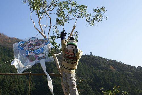 木に引っかかった凧をお父さんが取っています。