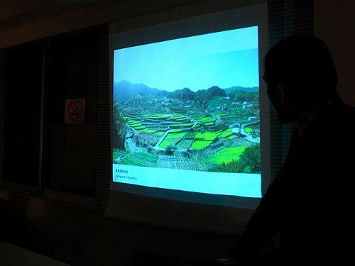 東京芸大の研究室で自ら立ち上げた「Beer&Talks」というセッションで、プロジェクト「空家町屋」のプレゼンをする坂東さん(右の黒い影)。江田の棚田風景、目を見張りますねぇ!(画像提供:坂東さん)