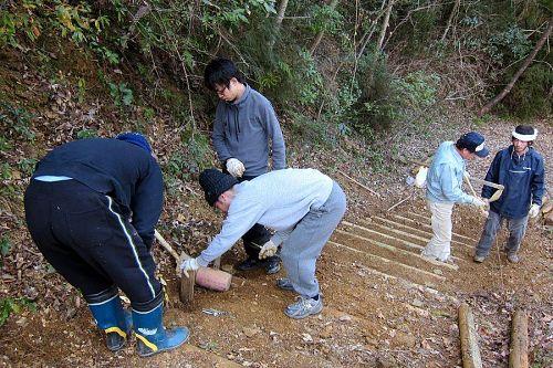 木製ステップの修繕をする塾生たち。左から長谷さん、宮部さん、西野さん、講師の森昌槻さん(グリーンバレー)とジュリアンさん。