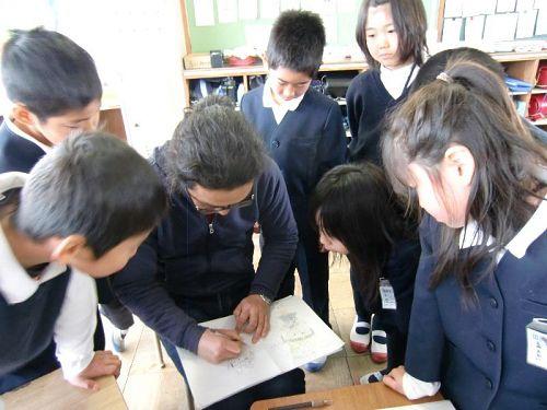 マンガを書く伸さんに集まる子どもたち。