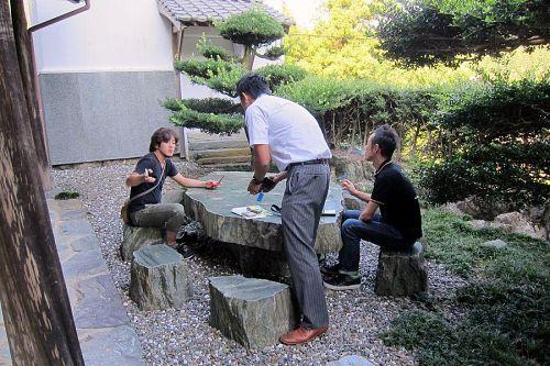 前庭の青石テーブルと腰掛けの周りでは、打ち合わせが始まっています。