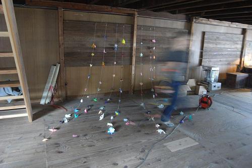 河野定子さんと一緒に折り紙を糸通ししてから安岐さんが天井につけた。