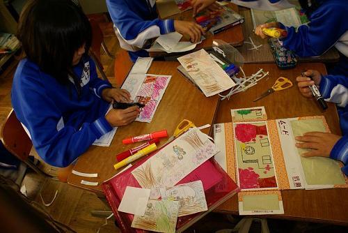 ティッシュの箱ほどの大きさの物をくりぬいてビニル状のものに神山の四季の絵を描きます。